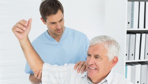 Male physiotherapist assisting senior man to stretch his hand in
