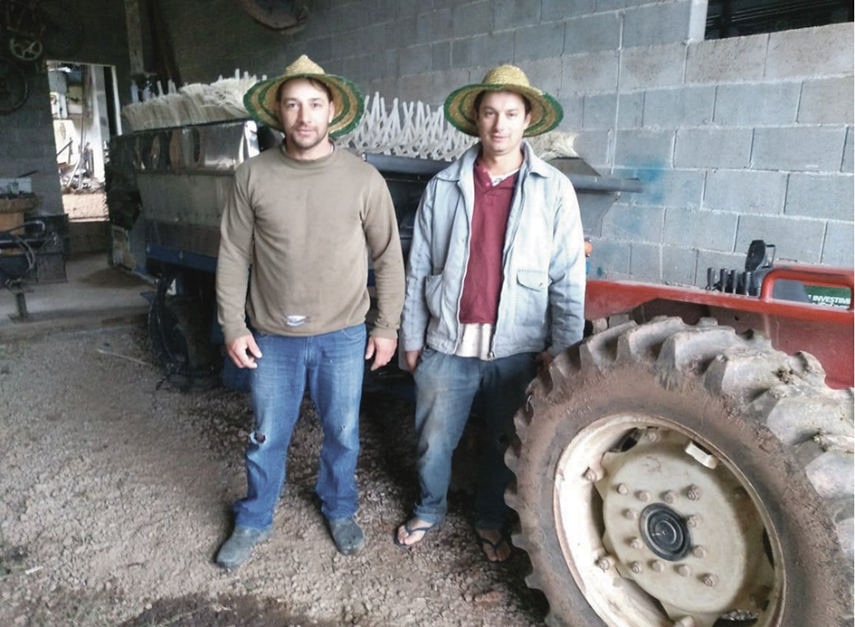 Os primos Marcos e Joemir Salton. Ao lado, a colheitadeira criada por eles.